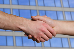 People shaking hands in front of a building