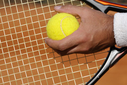 A tennis racket and ball held in a man's hands