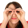 Woman holding her hands up to her eyes like glasses