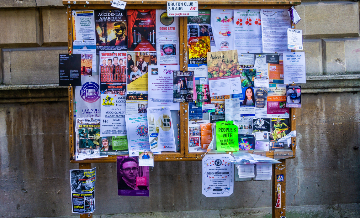 Notice board full of advertising ads, flyers and leaflets