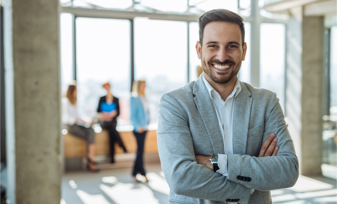 A business owner smiles happily in his office while his employees chat in the background.