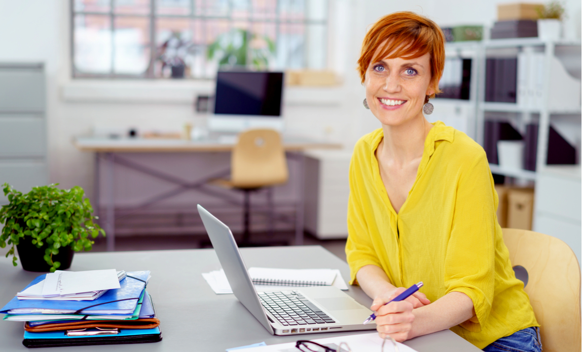 Happy smiling red haired woman in yellow blouse sitting at desk with laptop, eyeglasses and stacks of papers and folders