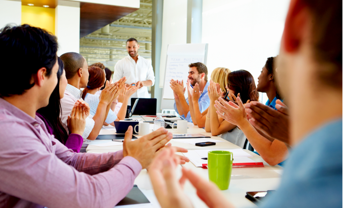 Satisfied business employees applaud after their colleague gives a successful presentation