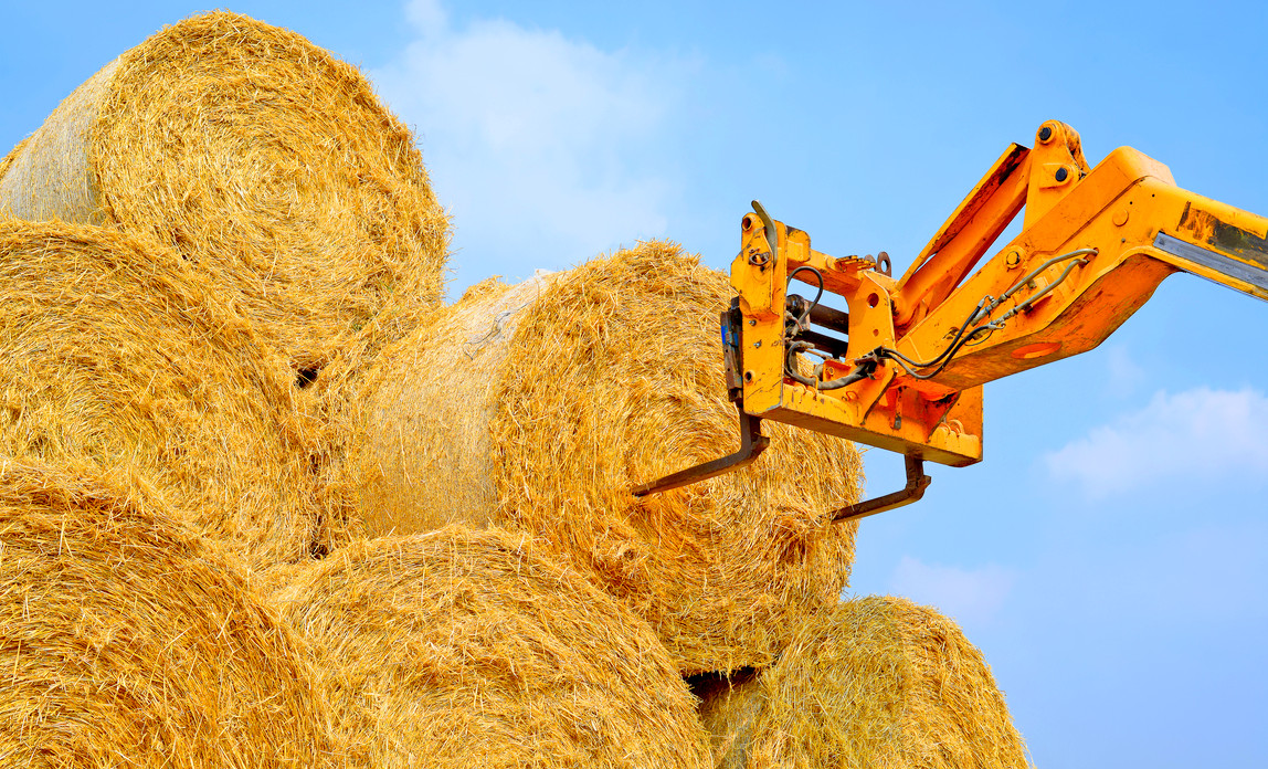 A yellow forklift moving hay bales on a sunny day