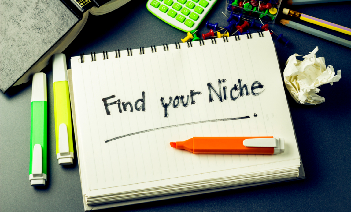 Handwritten 'find your niche' on a notepad on a desk