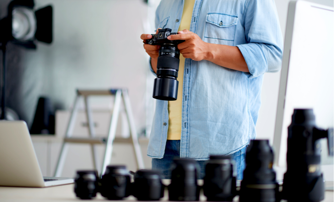 A professional photographer checks his camera equipment before taking photographs