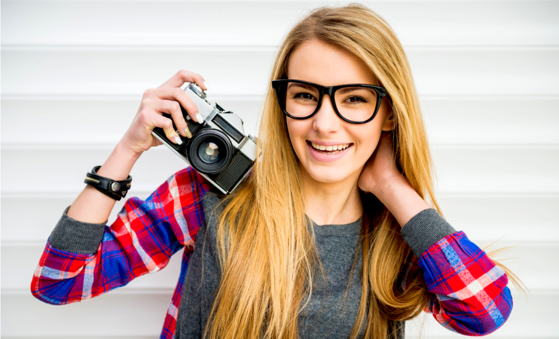 Young photographer using a retro film camera for her Instagram
