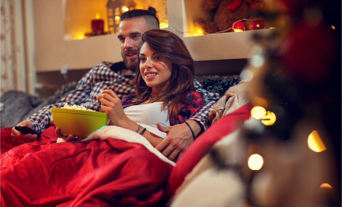 A couple relax and watch tv at Christmas time.