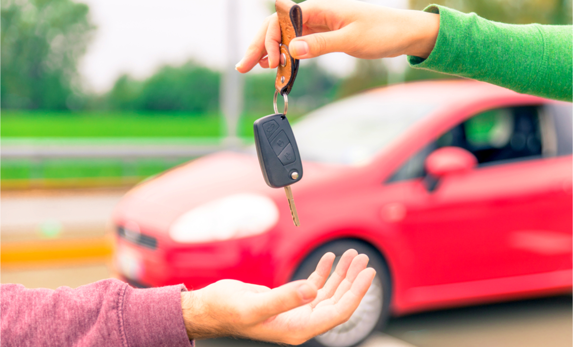 A car owner sells his used business vehicle and hands over the keys to its new owner.