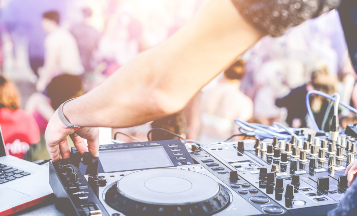 A DJ is mixing music at an outdoors party on his mixing desk