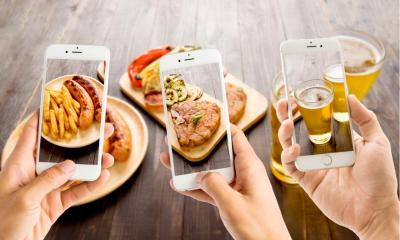 Multiple people taking Instagram photos of their food and drinks