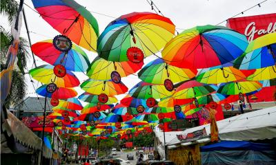 Rows of multicoloured umbrellas suspended in the air above a street