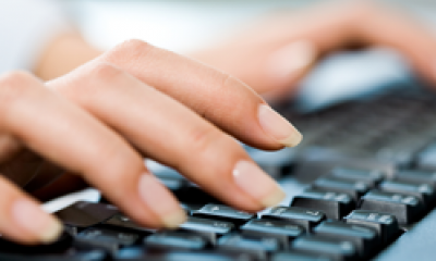 Fingers typing out web copy on a keyboard