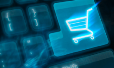 Symbol of a shopping trolly on a computer key representing online shopping and ecommerce