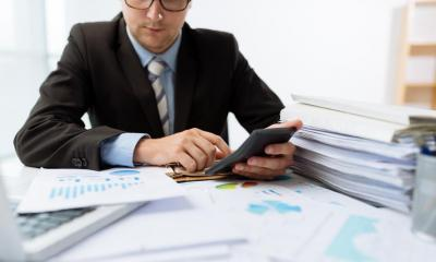 Male accountant using a calculator next to a laptop and stacks of paper