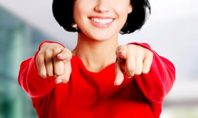 Woman in red top pointing with both hands addressing the camera