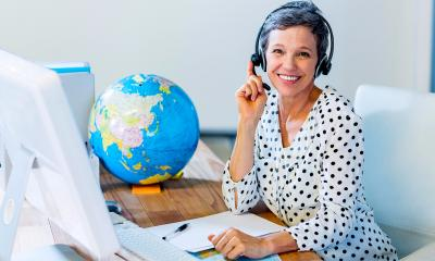 Female travel agent with headset on sat at her desk with a globe in the background