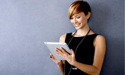 Woman in black top using her tablet to advertise on LinkedIn