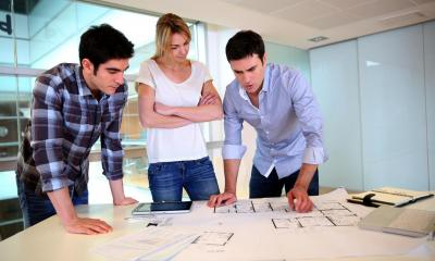 Group of architects looking at prints of a building plan