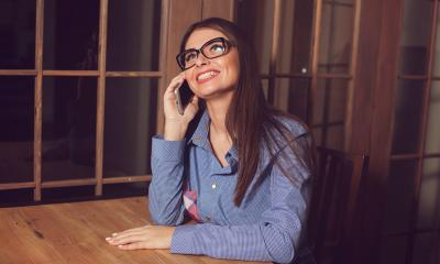 Woman in a blue shirt and glasses communicating with a customer over the phone