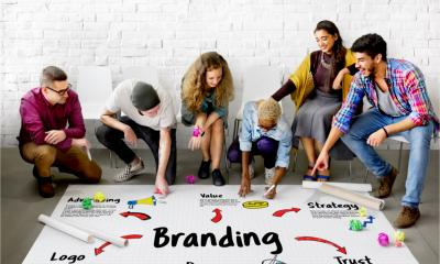 Group of people sat around a 'Branding' brainstorm on a large piece of paper