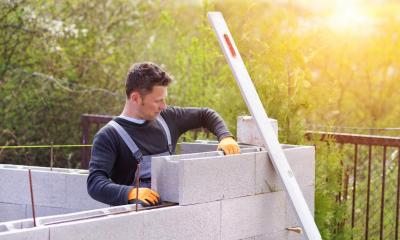 Male builder stacking breeze blocks on top of each other on a sunny day
