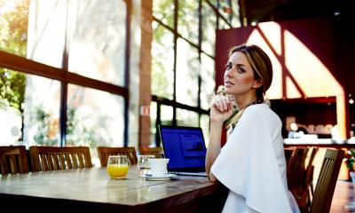 Woman in a white dress sat in an empty restaurant with a laptop and drink on the table