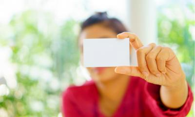 Woman holding out a business card towards the camera