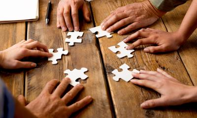Group of people holding different pieces of a white puzzle on a wooden table