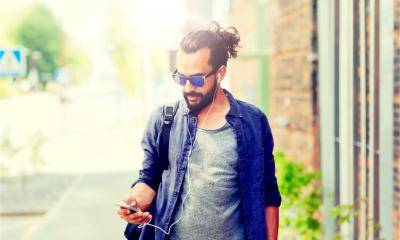 A man with earphones and smartphone walks whilst listening to a podcast.