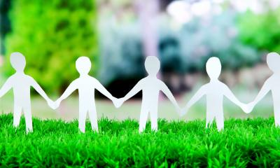 Paper chain cutout showing a team of people holding hands on fake grass
