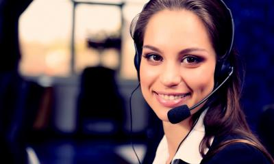 Female customer care worker with a headset on smiling at the camera