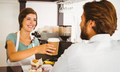 Barista handing a customer a coffee with a big smile