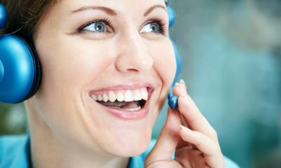 Smiling marketing manager using a bright blue headset to contact her customers