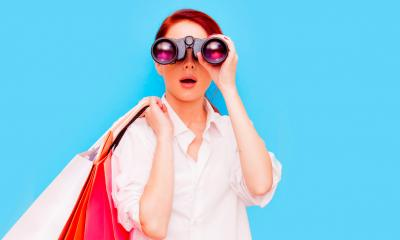 Woman in a white shirt holding bags looking through a pair of binoculars