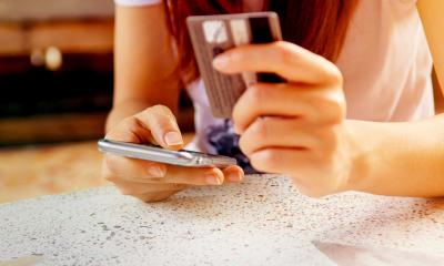 Woman holding her credit card in one hand and her phone in the other hand