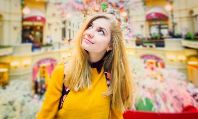 Woman with blonde hair in a yellow sweater looking up in a colourful exhibition