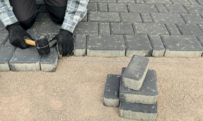 Person wearing gloves laying bricks on the floor to make a driveway or patio