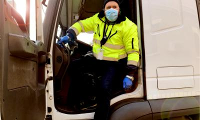 Delivery driver in a truck wears a face mask and protective gloves for coronavirus