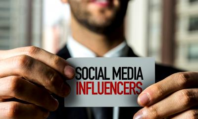 "Man holding a ""social media infuencers"" card"