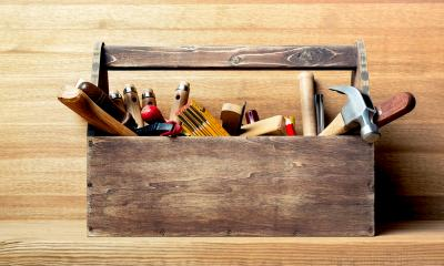 Wooden tool box holding an assortment of tools