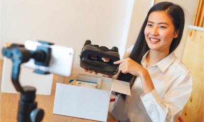 A young Asian woman films an explainer video and unboxing of a new product.