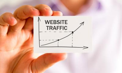 Person holding a business card with 'WEBSITE TRAFFIC' written on it