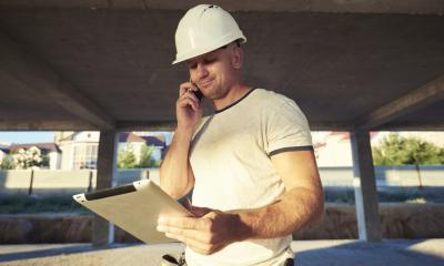 Man in a white hardhat on the phone while holding a tablet in the other hand