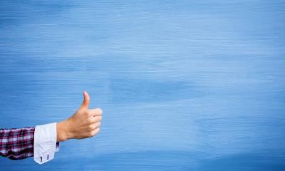 Person holding their thumb up in front of a blue back ground imitating the Facebook logo