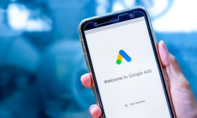 Hand holding mobile with the Google ads app on the screen