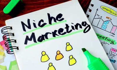 'Niche Marketing' written in black pen in a notebook on a wooden table