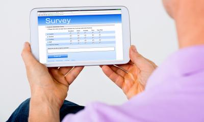 Man in a purple top using a tablet to complete a customer questionnaire survey
