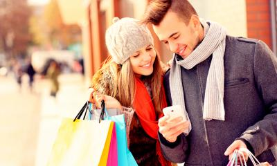 Man and a woman wearing winter clothes holding shopping bags while looking at a phone