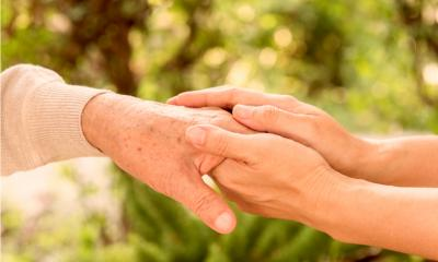 A person holding an older persons hand with blurred trees in the background